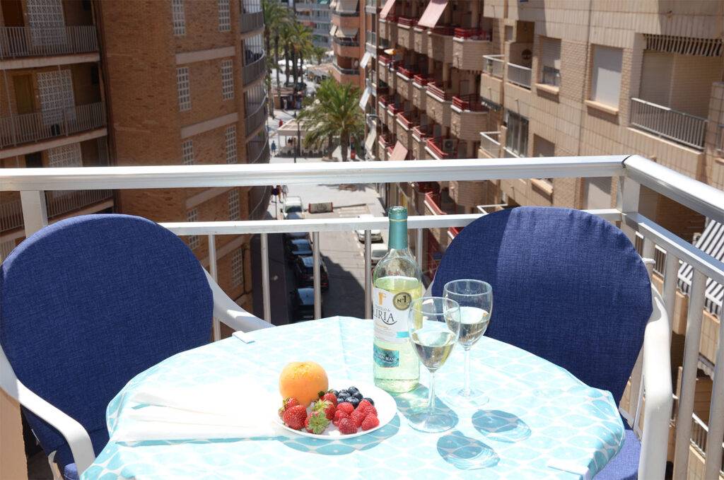 Wine and berries on a table on the balcony.